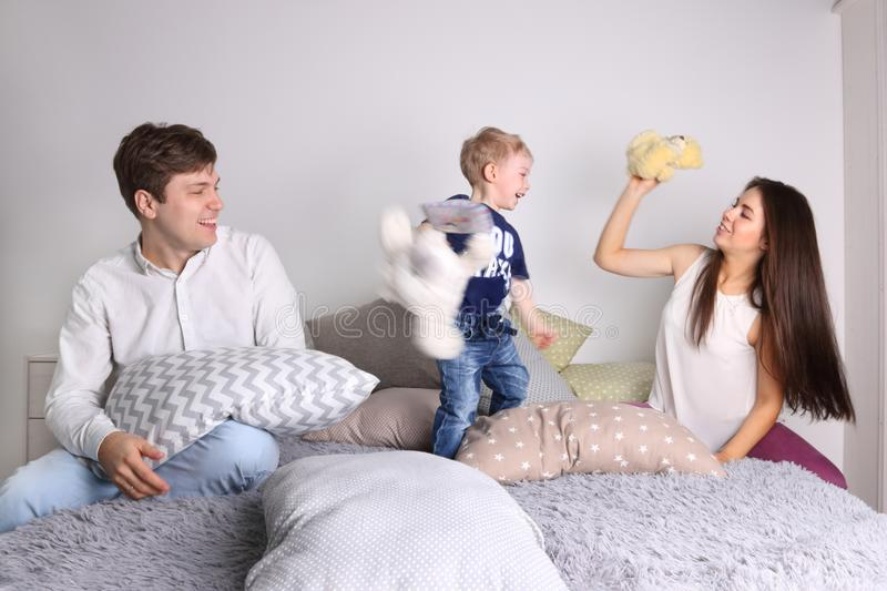 Young father, mother, little cute son play on bed royalty free stock images
