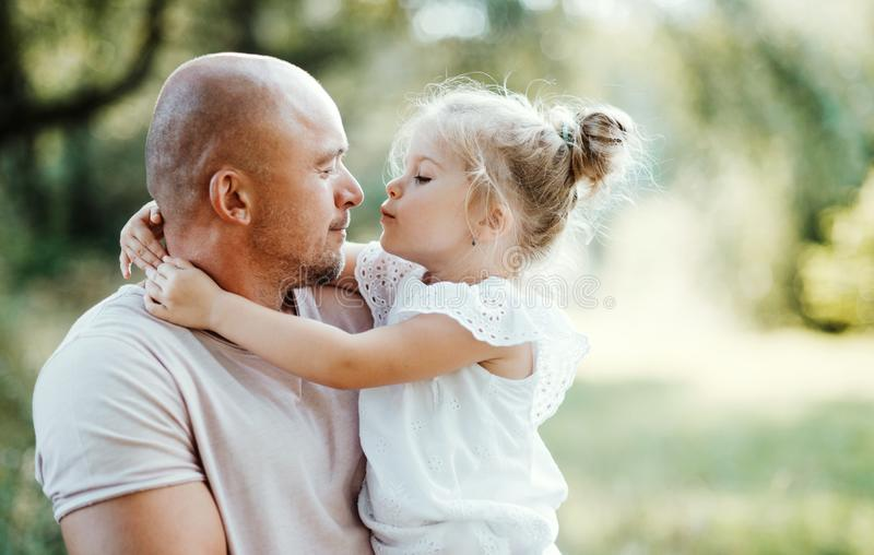Young father in nature holding small daughter in the arms. stock images