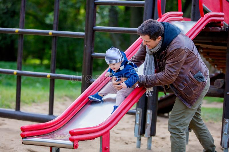 Young father play with a child on a playground royalty free stock photo