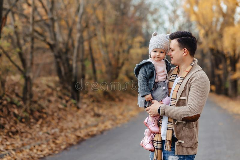 Young father play with little daughter at autumn park road stock photography