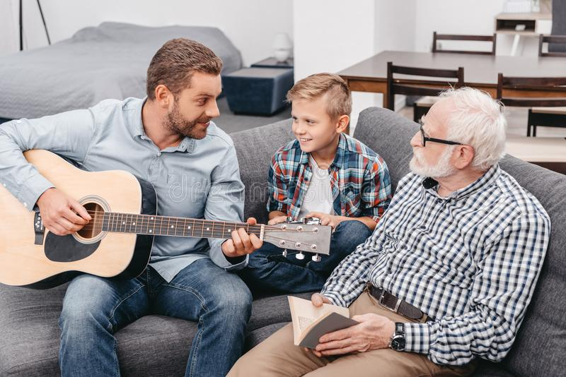 Young father playing guitar while little son and grandfather are royalty free stock photos