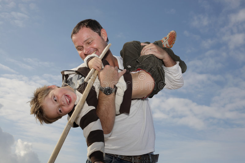 Young father playing with his son. On the beach against sky background royalty free stock photography