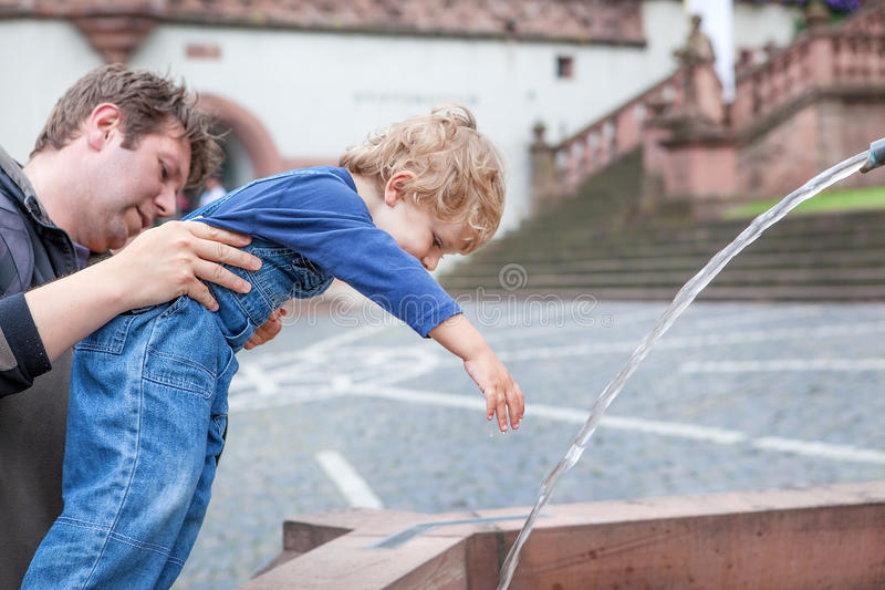 Young father playing with toddler boy with water of fountain royalty free stock images