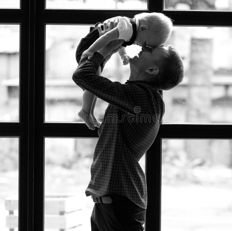 Young father plays with his little son and throws up his stock photography