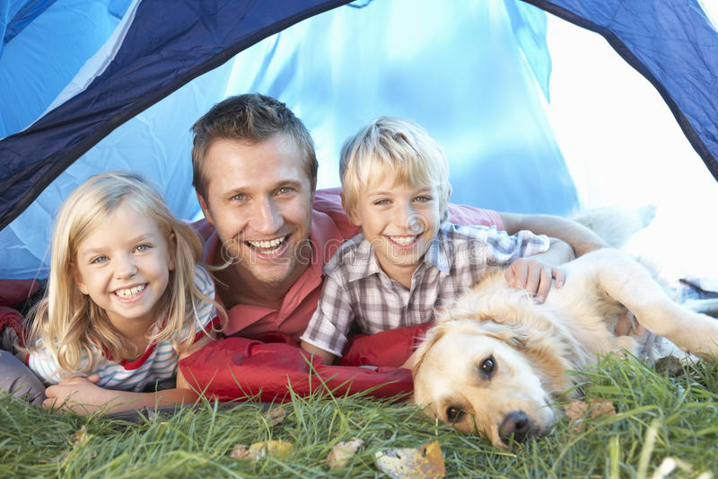 Young father poses with children in tent royalty free stock image