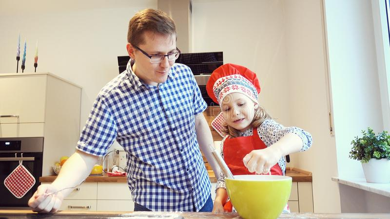 Young father with pretty little daughter backing cookies and having funat home stock photo