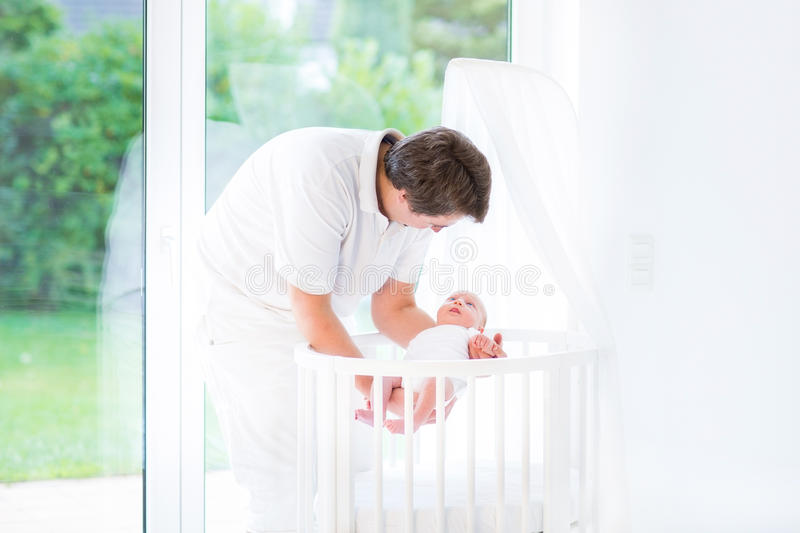 Young father putting his newborn baby in crib. Young smiling father putting his newborn baby in a white round crib royalty free stock photo