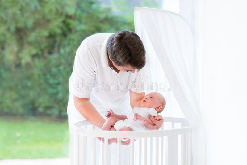 Young father putting his newborn baby into crib. Young father putting his newborn baby into a white round crib next to big window into a garden royalty free stock images