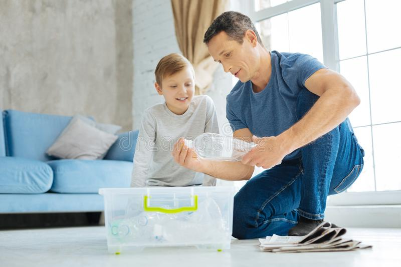 Young father showing his son how to crush plastic bottle. Nice teacher. Pleasant caring young father sitting on the table next to his son and showing him how to royalty free stock photos