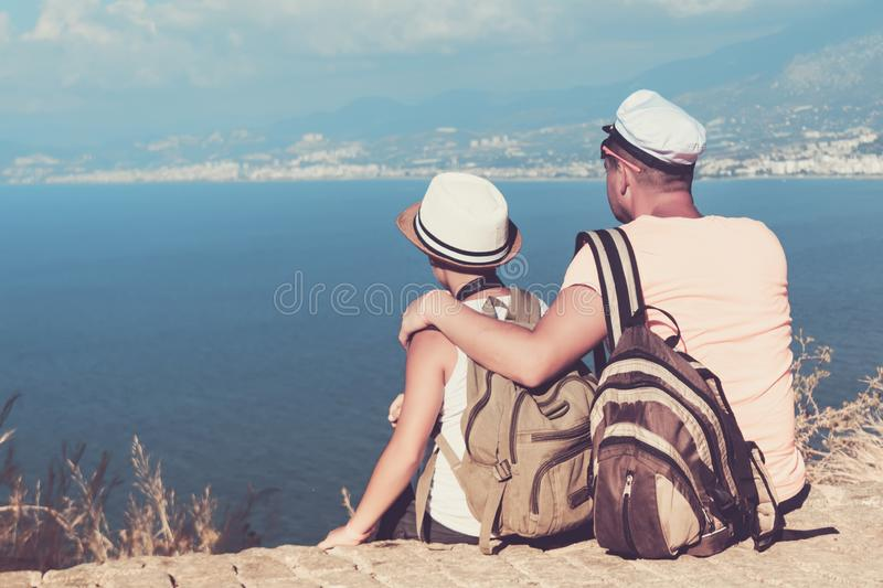 Young father and son with backpacks are sitting on the beach against the backdrop of the sea. Family travel concept royalty free stock images
