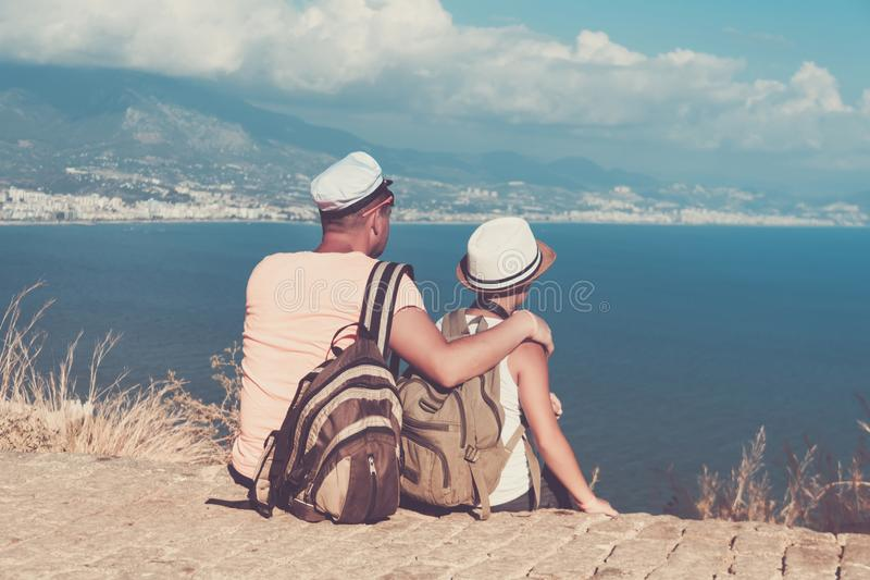 Young father and son with backpacks are sitting on the beach against the backdrop of the sea. Family travel concept stock photos