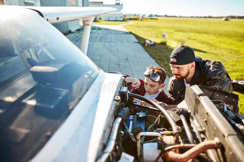 Young father and son trying to fix electrical wire system of light aircraft royalty free stock photo
