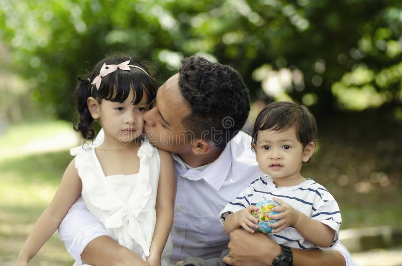 Young father spending time with his children at park during weekend royalty free stock image