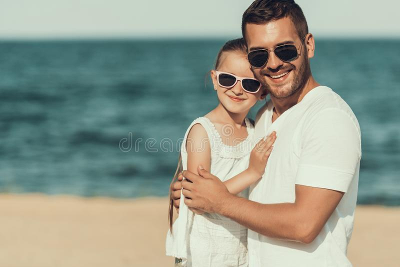 Young father in sunglasses hugs daughter on beach near sea. royalty free stock photography