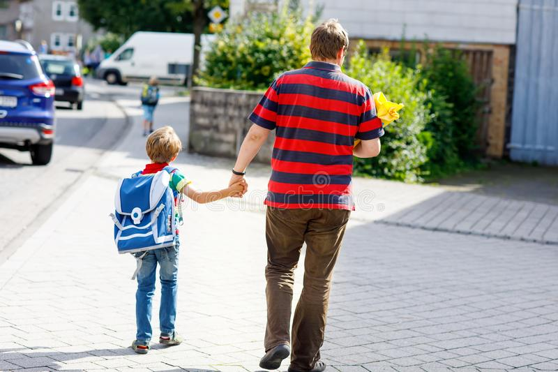Young father taking child, kid boy to school on his first day. Parent taking child, kid boy to school. Pupil of primary school go study. Father holding hand of royalty free stock photos