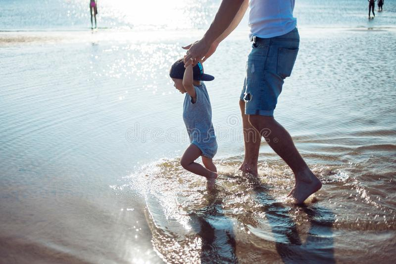 Young father teach baby to walk. man with a child playing by the sea. Young father teach baby to walk. Young happy family walking on the beach royalty free stock photos