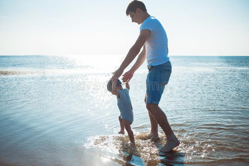 Young father teach baby to walk. man with a child playing by the sea. Young father teach baby to walk. Young happy family walking on the beach stock images