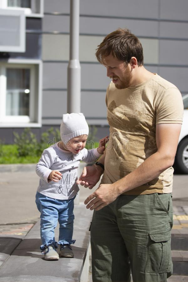 A young father teaches his child to walk. Little girl a boy in jeans and a hat walks with dad. Family on a walk, warm sunny day in royalty free stock photography