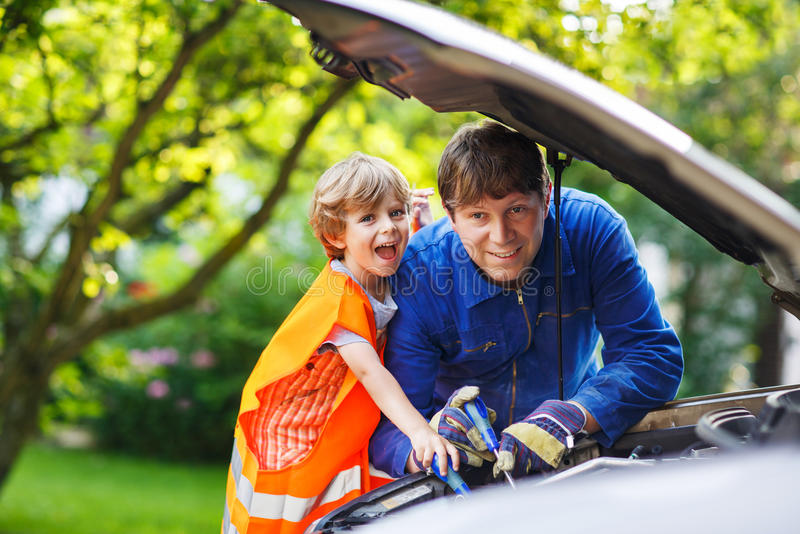 Young father teaching his little son to change motor oil for Family motors auto repair