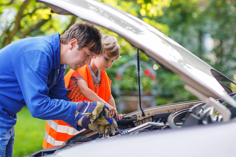 Young father teaching his little son to repair motor oil in family car royalty free stock photos