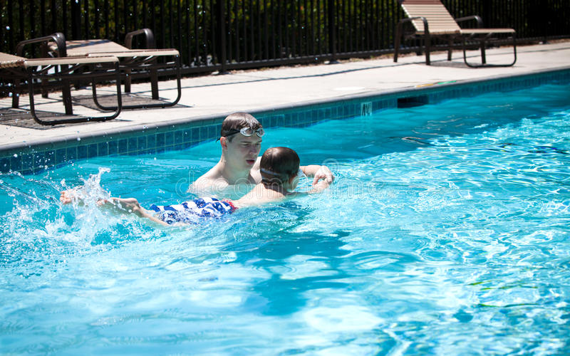 Young father teaching little boy to swim stock images