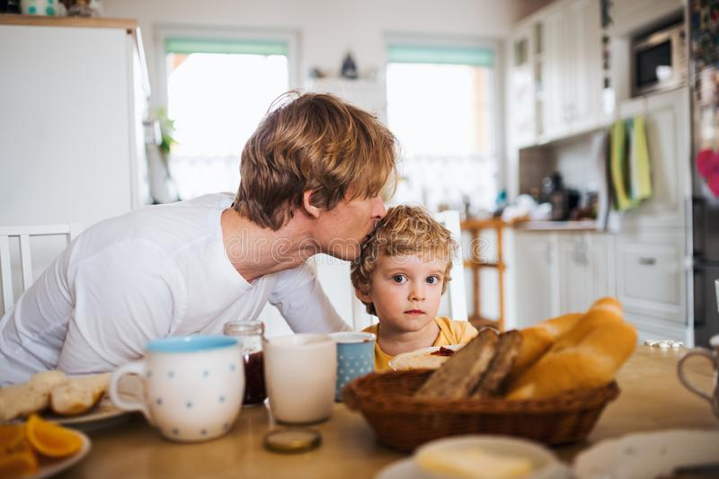 Young father with a toddler son eating breakfast indoors at home. stock photography