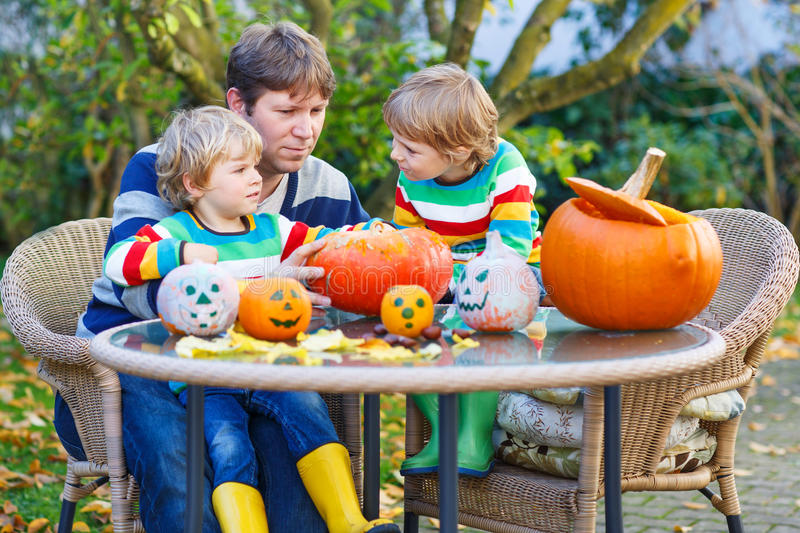 Young father and two little sons making jack-o-lantern for halloween in autumn garden royalty free stock photos