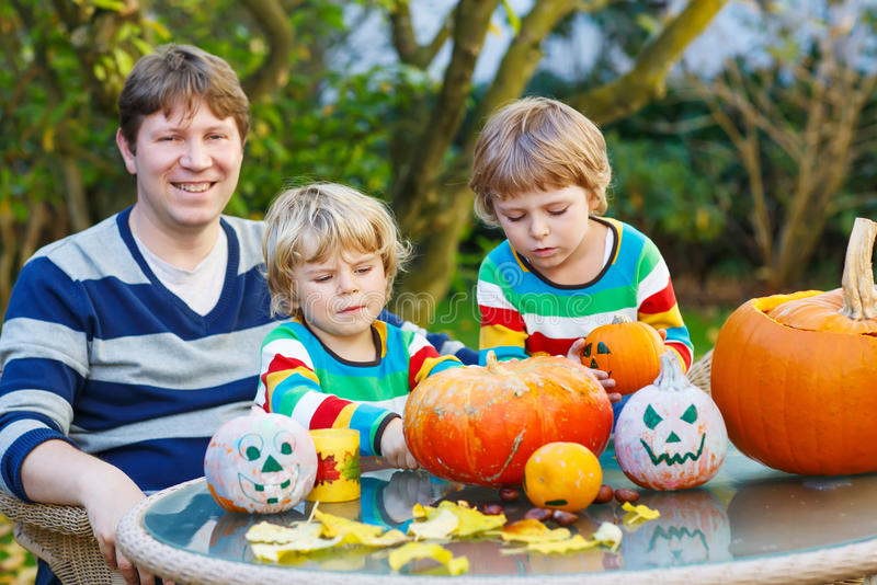 Young father and two siblings making jack-o-lantern for halloween in autumn garden stock photos