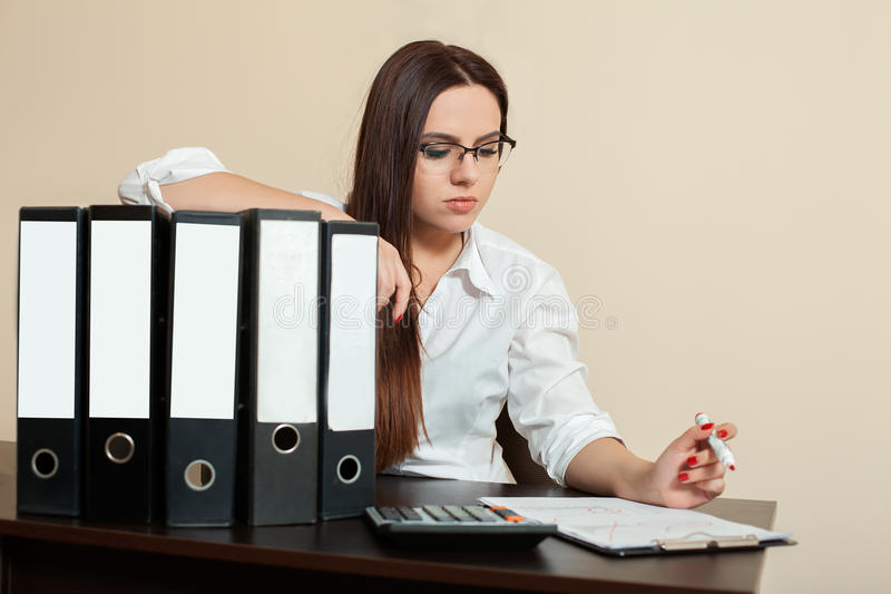 Young female accountant hugs documents folders. In office stock image