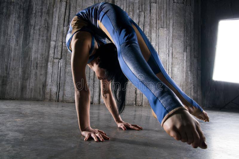 Young extremely flexible female acrobat standing on hand over gray background in photo studio royalty free stock images