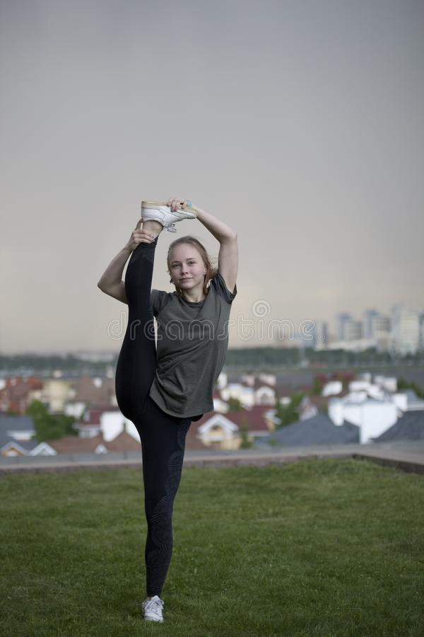 Young female acrobat standing on the leg in twine on background cityscape stock images