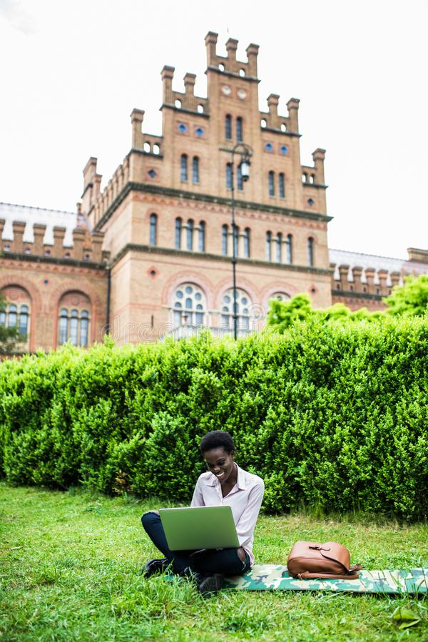University life. Young student female african american woman enjoying a sunny day at the campus, working on laptop. Young female african american woman enjoying stock image