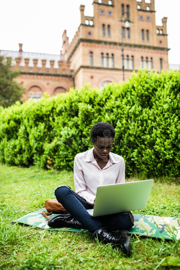 University life. Young student female african american woman enjoying a sunny day at the campus, working on laptop. Young female african american woman enjoying royalty free stock photos