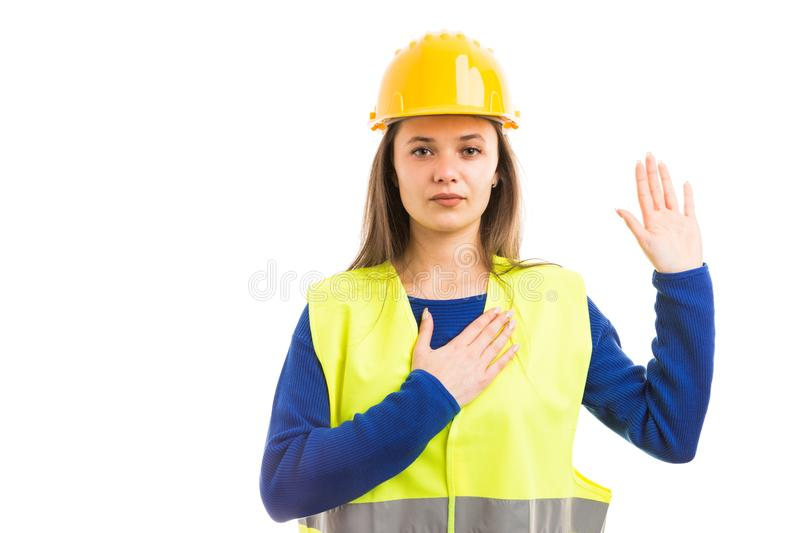 Young female architect making vow gesture. Young female architect or engineer making vow gesture with raised hand as professional sewar promise isolated on white royalty free stock photo