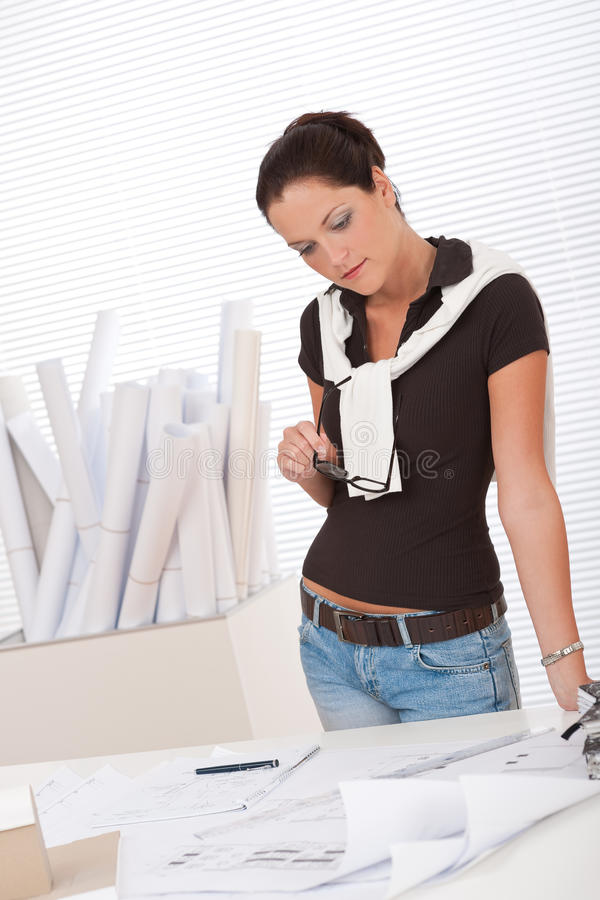 Young female architect studying plans royalty free stock photo