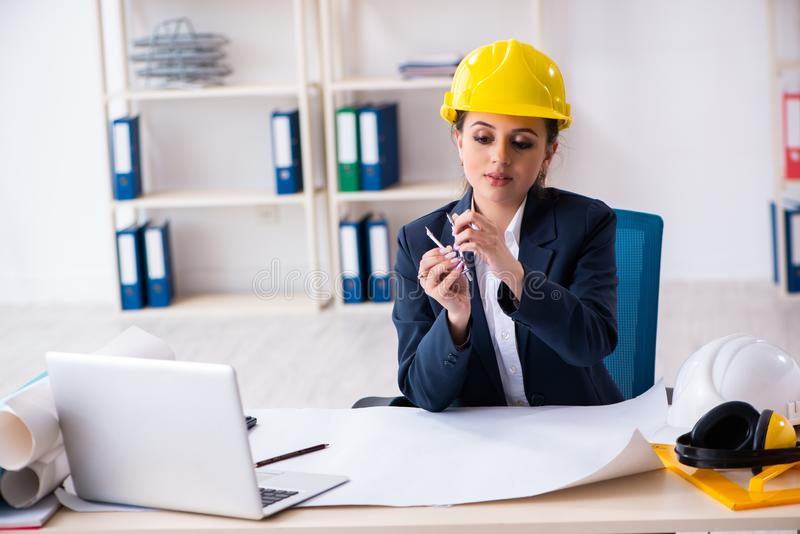 The young female architect working in the office royalty free stock images
