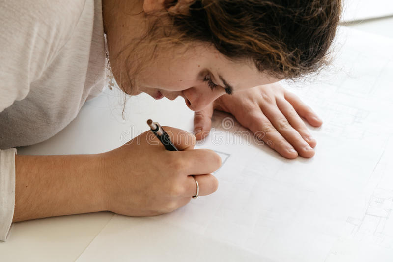 Young female architect working on sketches royalty free stock photo