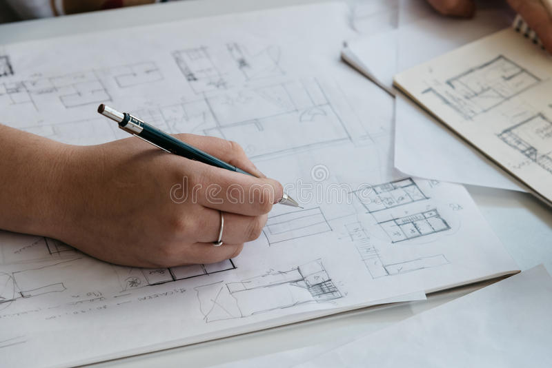 Young female architect working on sketches royalty free stock photography