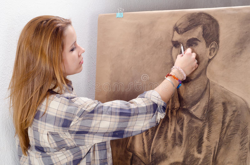 Young female artist drawing man portrait stock photos