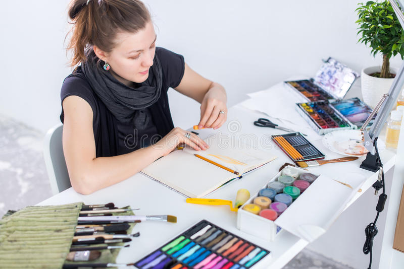 Young female artist drawing sketch using sketchbook with pencil at her workplace in studio. Side view portrait of stock photos