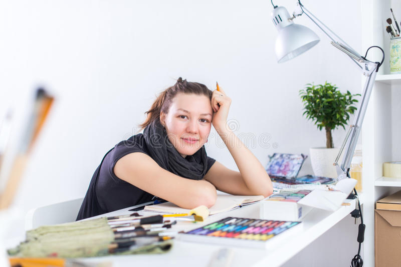 Young female artist drawing sketch using sketchbook with pencil at her workplace in studio. Side view portrait of royalty free stock photography