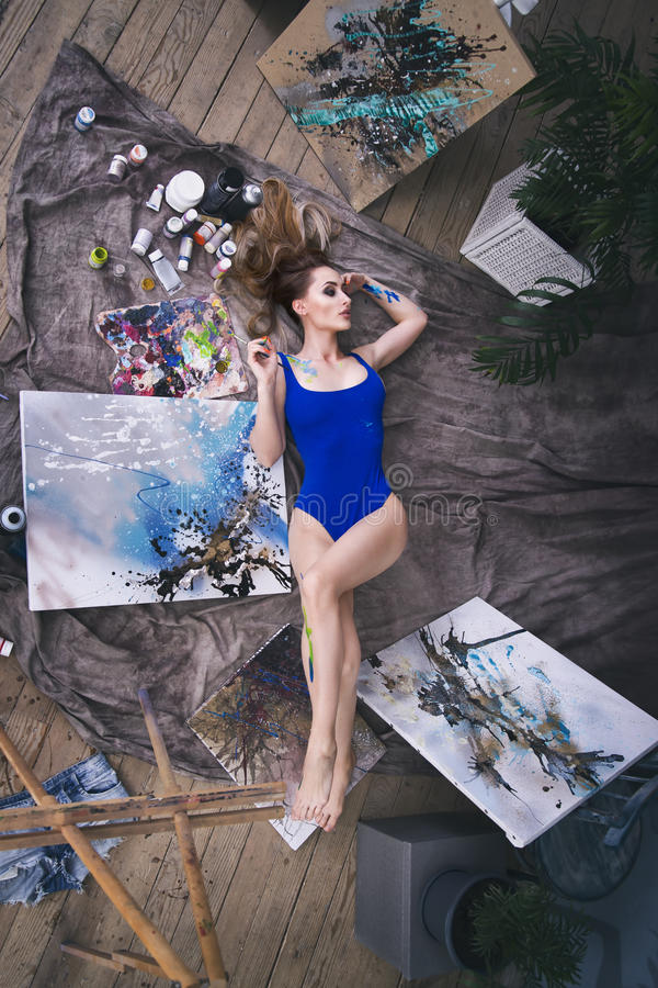 Young female artist painting abstract picture in studio, beautiful woman portrait. Toned image stock photography