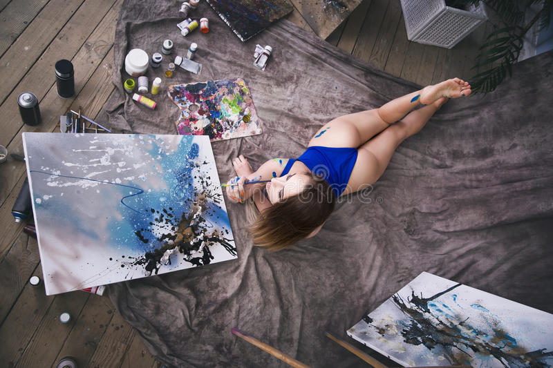 Young female artist painting abstract picture in studio, beautiful woman portrait. Toned image stock image