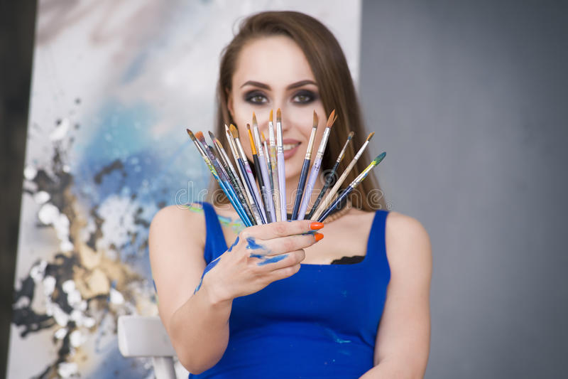Young female artist painting abstract picture in studio, beautiful woman portrait. Toned image royalty free stock photos