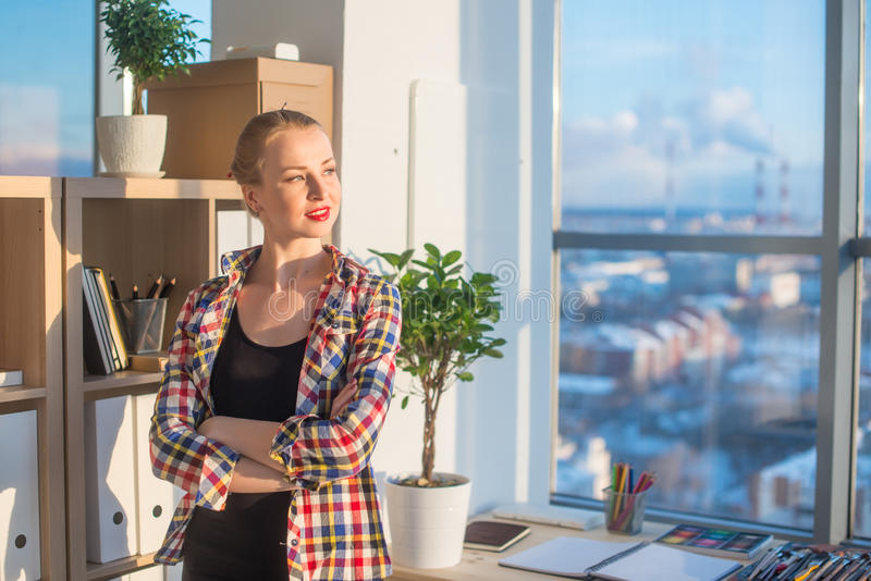 Young female artist standing at art studio, holding arms folded across, her workplace, smiling, looking aside. Designer. With artistic tools on work-table ready stock photo