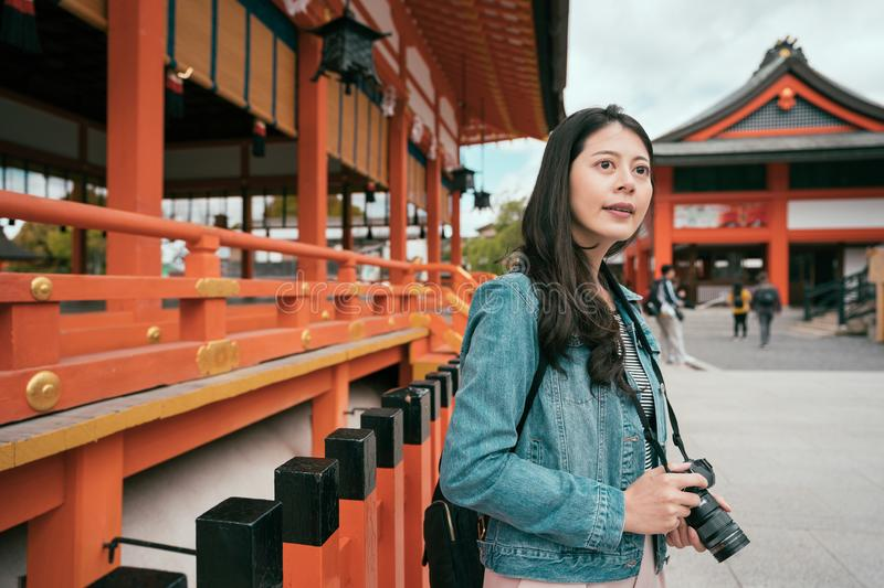 Young female asian photographer shooting. By slr camera sightseeing in temple in kyoto japan. girl looking around in fushimi inari shrine. red wooden japanese royalty free stock image