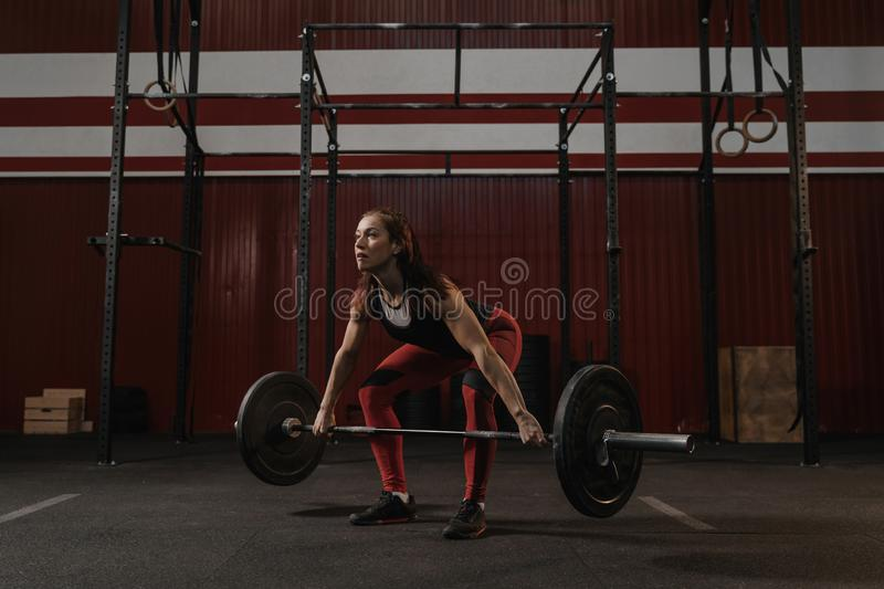 Young female athlete doing deadlift exercise. Strong woman lifting heavy barbell at crossfit gym royalty free stock image