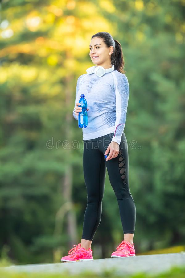 Young female athlete drinks water after training royalty free stock photo