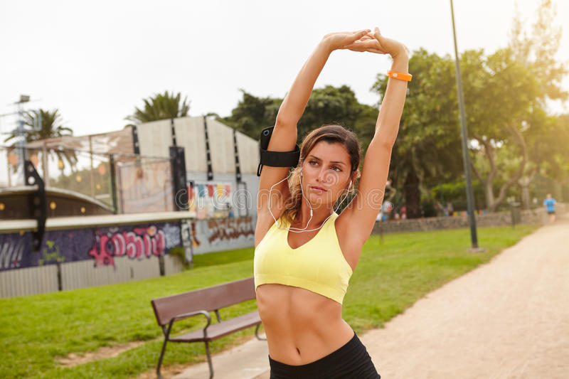 Young female athlete exercising in the park stock image