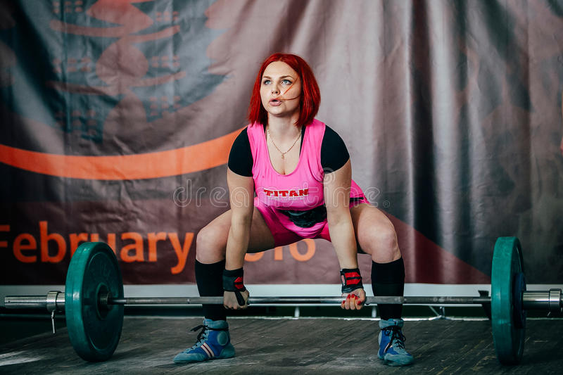Young female athlete performs deadlift barbell stock photography